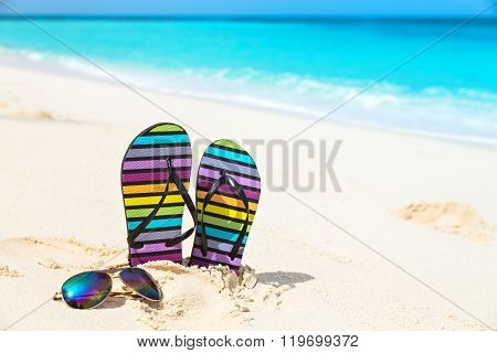 Multicolored Flip-flops And Sunglasses On A Sunny Beach..tropical Beach Vacation And Travel Concept.