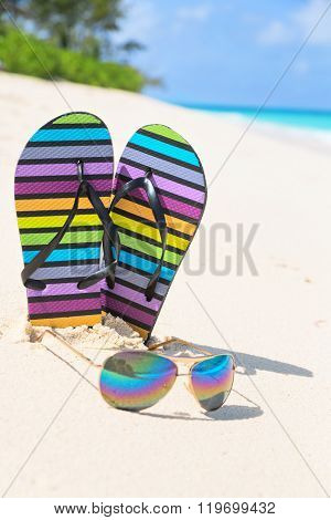 Multicolored Flip-flops And Sunglasses On A Sunny Beach..tropical Beach Vacation And Travel Concept,