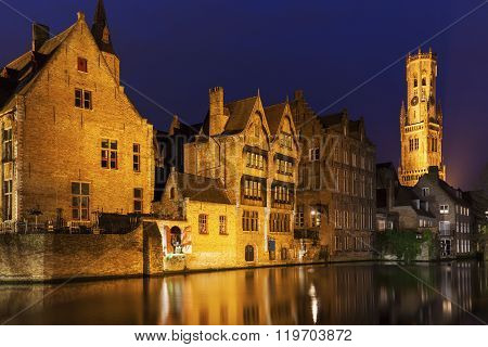 Belfry of Bruges reflected in the canal. Bruges Flemish Region Belgium