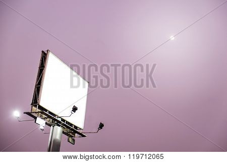 Blank white billboard on evening sky with moonshine