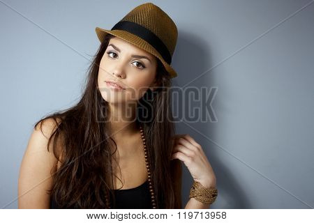 Attractive young woman in straw hat with long hair, looking at camera.