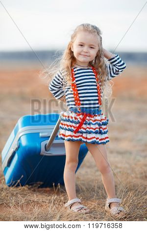 The little girl with a big blue suitcase