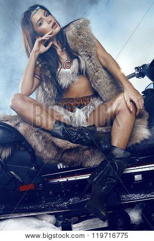 Young Beautiful woman posing on snowmobile