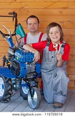Man And Young Boy Servicing A Small Tiller Machine