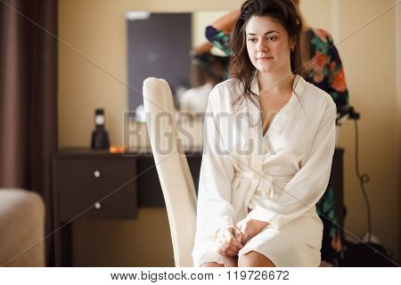 The bride in white bathrobe with her hair done at morning. Wedding preparations.