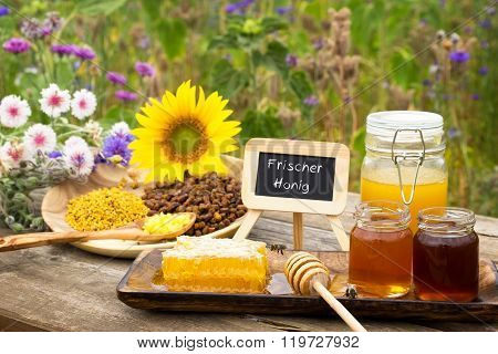 Various bee products on a wooden table with a slate with Frischer Honig (fresh honey in German) ** Note: Shallow depth of field