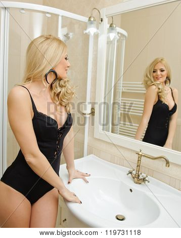 Sexy beautiful young woman wearing black lingerie in bathroom. Sensual blonde in front of the mirror