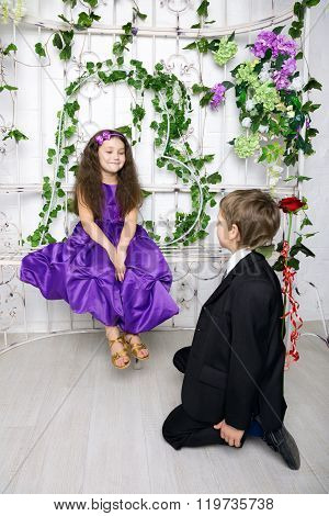 Boy Gives To Girl A Rose Flower. Little Enamored.