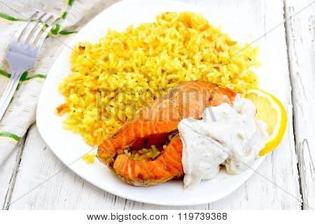 Salmon with lemon and rice on light board