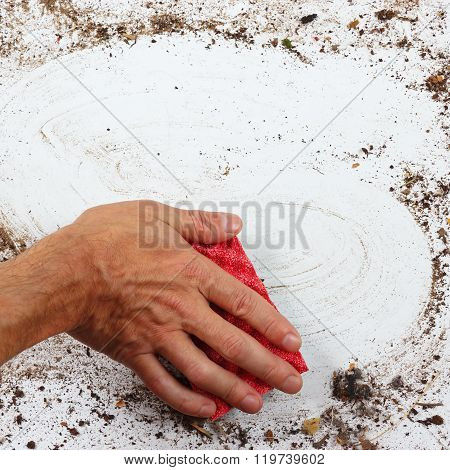 Hand with red sponge wiping heavily dirty surface