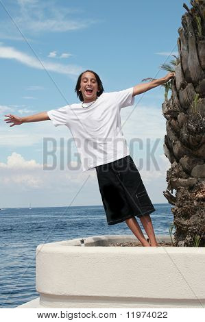 A boy leaning toward the ocean with arms outstretched.