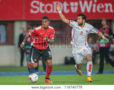 VIENNA, AUSTRIA - OCTOBER 12, 2014: Marko Basa (#5 Montenegro) and Rubin Okotie (#9 Austria) fight for the ball in an European Championship qualifying game.