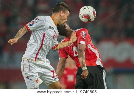 VIENNA, AUSTRIA - OCTOBER 12, 2014: Rubin Okotie (#9 Austria) and Marko Simic (#23 Montenegro) fight for the ball in an European Championship qualifying game.