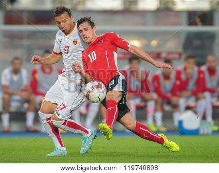 VIENNA, AUSTRIA - OCTOBER 12, 2014: Elsad Zvertovic (#17 Montenegro) and Zlatko Junuzovic (#10 Austria) fight for the ball in an European Championship qualifying game.