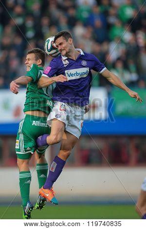 VIENNA, AUSTRIA - NOVEMBER 9, 2014: James Holland (#25 Austria) and Louis Schaub (#10 Rapid) fight for the ball in an Austrian soccer league game.
