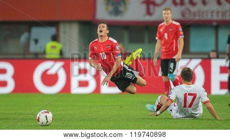 VIENNA, AUSTRIA - OCTOBER 12, 2014: Elsad Zvertovic (#17 Montenegro) fouls Zlatko Junuzovic (#10 Austria) in an European Championship qualifying game.