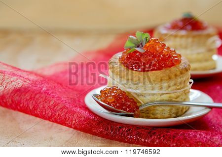 Tartlets with red caviar on plate.