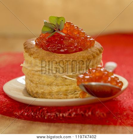 Tartlet with red caviar on plate.