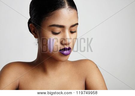 Woman With A Lilly Primer For Correction Of Skin Tone On A Cheek