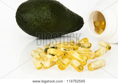 Cod liver oil omega 3 gel capsules with avocado isolated on white background