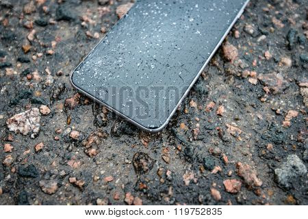 Phone With Broken Screen On Asphalt