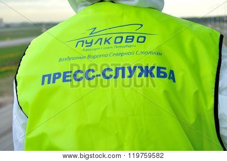 The Inscription On The Back Of Bright Green Vest Press Service Of Pulkovo Airport Of Saint-petersbur
