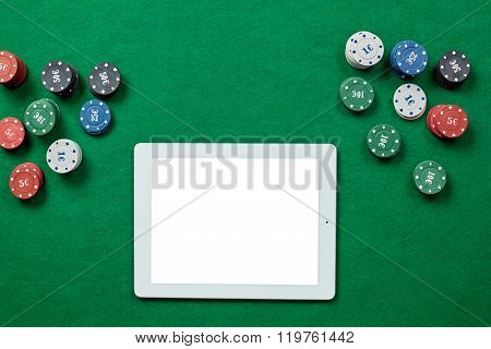 Online poker game with digital tablet and stacks of chips.