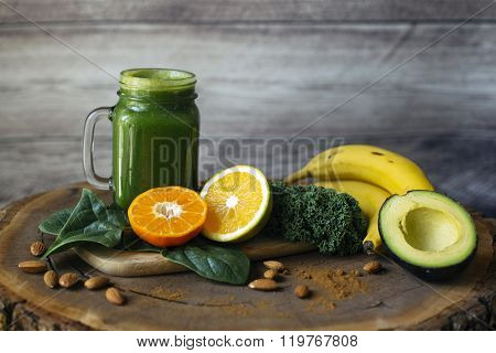 Green smoothie and ingredients on a wooden table: spinach, kale, orange, tangerine, bananas, cinnamon and avocado.