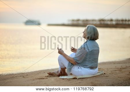Mature woman meditating on beach