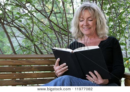 A beautiful woman enjoying a good book on her porch swing.