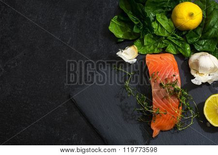 Raw Salmon Fillet With Thyme, Garlic, Lemon And Spinach On A Dark Slate Plate, View From Above, Gene
