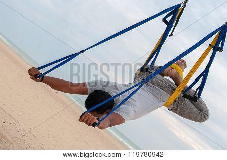 Anti-gravity Yoga, man doing yoga exercises on the sea background
