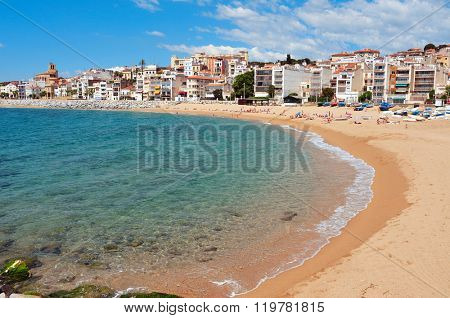 SANT POL DE MAR, SPAIN - MAY 23, 2015: A view of Platja de les Barques beach in Sant Pol de Mar, Spain, where some people are sunbathing. The boats, barques in Catalan, give name to this beach