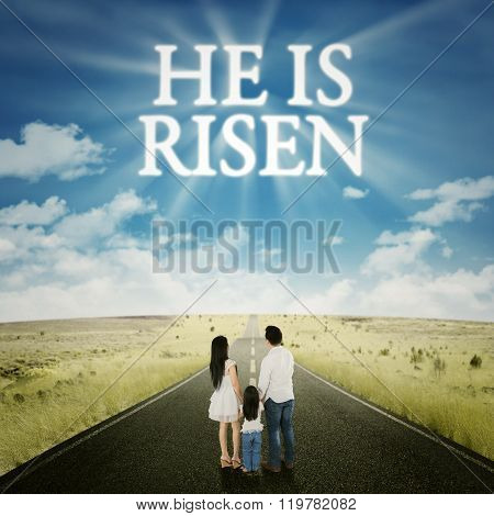 Family Standing On The Road With Text He Is Risen