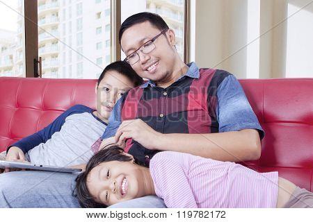 Father Spoiling His Children On The Couch