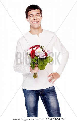 Young hispanic man wearing glasses, blue jeans and white long sleeve, standing with hand on his hip, holding bunch of flowers in other hand and smiling - dating concept