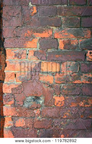 Obsolete brick wall painted in orange and dark violet