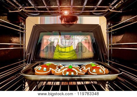 Baking Gingerbread man in the oven, view from the inside of the oven. Cooking in the oven. Focus not on cookies focus on woman