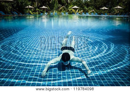 Man dives into a swimming pool views over the water and under water. Maldives.