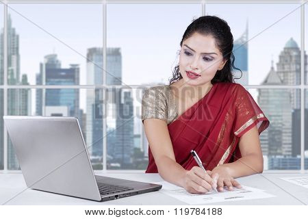 Indian Young Woman Writing Document In Office