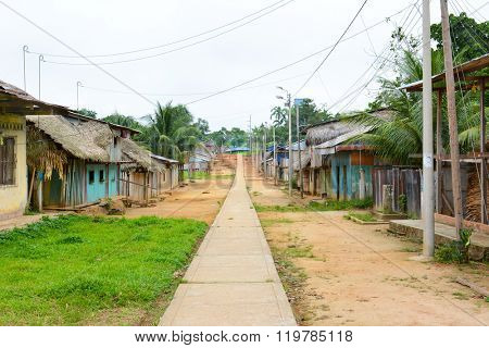 SANTA ANA VILLAGE, PERU - OCTOBER 14, 2015: Sidewalk running between homes. Colorful wooden homes with thatched or tin roofs are common in the Amazon.