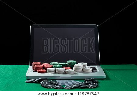 Casino chips and cards on keyboard notebook at green table.