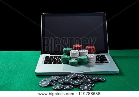 Casino chips on keyboard notebook at green table.