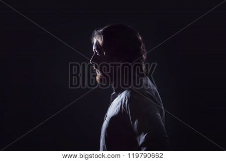 Man with  beard, profile  on  dark background, the silhouette.
