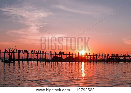 Bridge U-Bein teak bridge is the longest. Sunset with silhouettes of people unrecognizable