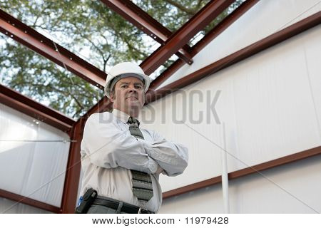 A construction inspector standing inside an unfinished steel frame building. `