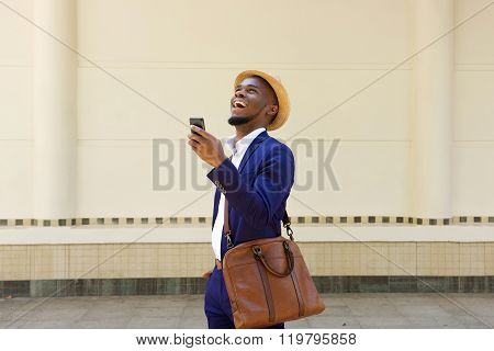 African Businessman Walking With A Cellphone And Bag