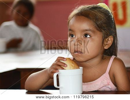 IQUITOS, PERU - OCTOBER 12, 2015: Snack time in the Santa Ana Village Kindergarten. A young girl has a roll and milk.