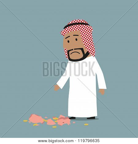 Arab businessman with broken piggy bank