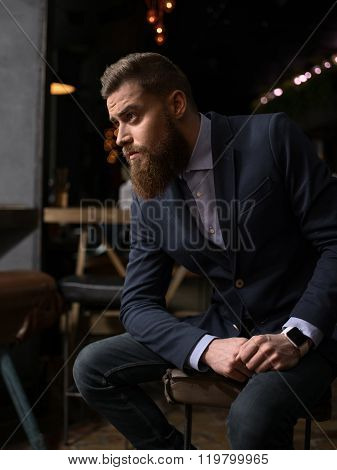 Cheerful bearded businessman is waiting in cafe